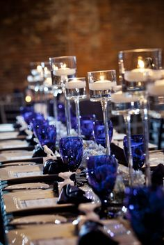 A row of pedestal glasses holding floating candles and gorgeous cobalt blue water glasses.  Bold by Design: June 2010