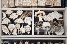 Stock Photo : Various plywood toys with pyrograph-made patterns and lines lay ready for painting in wooden box.