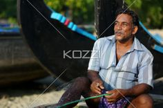 smiling at work - A man smiles while repairing his fishing net on Pollethai Beach, India.