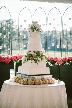 White five tier wedding cake with a floral breakup https://www.thecelebrationsociety.com/weddings/flower-filled-white-wedding-forest-heights-country-club-statesboro-ga/