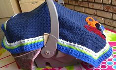 Keep baby protected from wind or bright sun when carrying in the car seat and, as pointed out by fellow Raveler lalael, the prying eyes of strangers at the supermarket!!! The dark main body of the blanket tent keeps out the bright lights, and the textured stitch makes it more dense and heavier to keep the wind out. Yardage is not yet given as it hasn't been tested, but I used less than one skein of the Caron One Pound and then smaller amounts of other yarns for the edging and appliques.