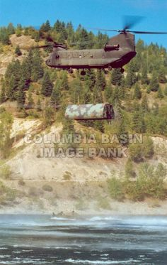 Canadian Armed Forces Chinook helicopter carrying a barge over the Arrow Lakes near Castlegar British Columbia during exercises in 2002: Columbia Basin Institute of Regional History