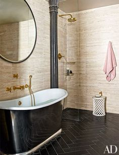The master bath, featuring travertine walls and a black limestone herringbone floor, is outfitted with a Jacques Garcia mirror by Baker, a tub and fittings by Waterworks, and a taboret by Paul Mathieu for Stephanie Odegard Collection.