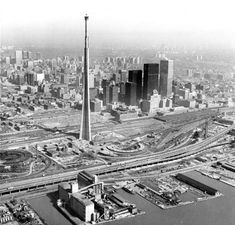 Toronto's CN Tower under construction. Two Train roundhouses below.