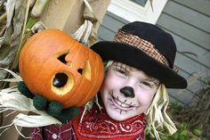 A kid dressed up as a scarecrow, holding a pumpkin.