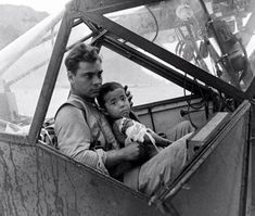 An American soldier cradles a wounded Japanese boy and shelters him from the rain in an airplane cockpit during the Battle of Saipan while waiting to transport him to a field hospital, July Photo by Peter Stackpole. Nagasaki, Hiroshima, World History, World War Ii, History Pics, Ww2 History, Military History, Ancient History, Gi Joe