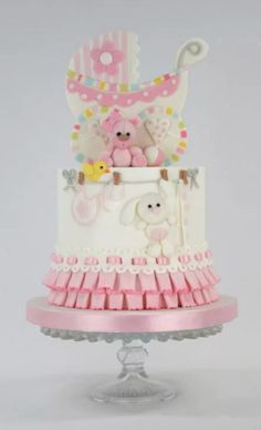 Cake for a baby girl. Box pleats and ribbon insertion techniques used for the ruffles at the base of the cake, and 2D and 3D techniques for the pram and toys on top of the cake