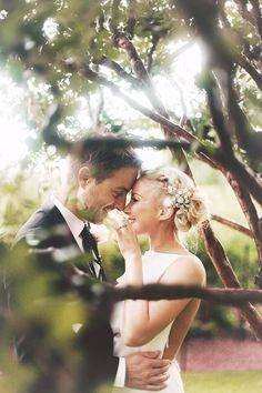 This is a super cute picture of the bride and groom. Outdoors in/around trees. Love it! Wedding photography.