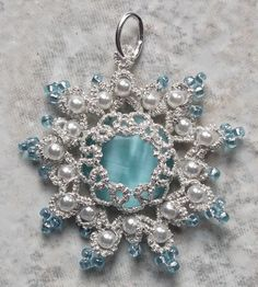 "Silvery Snowflake This pendent is another favorite. Tatsmithing looks so elegant! This one was made with two strands of silver sewing thread and a blue cats-eye. The pendent is 1 3/8"" in diameter. for sale on face book: west pine creations"