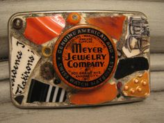 Mosaic belt buckle with Meyer Jewelry tin in orange and black, mosaic art.