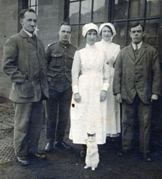 Two wounded soldiers, nurses and cat, WW1