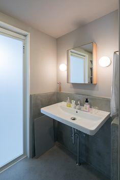 洗面所にもモルタル左官を入れて。ミラー付きの収納は「ザ・コンランショップ」のもの。