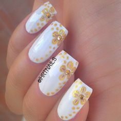 Pretty looking white and gold nail art designs in flower patterns. The nails have white base color and is topped with gold glitter polish that form a shape of a flower.