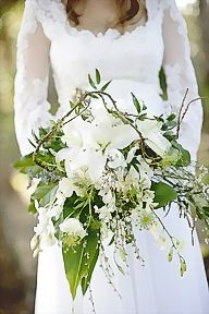 This bridal bouquet appears to have 3 white lilies with various fresh greenery - a loose hand-tied bouquet that is so pretty