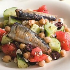 The fresh, tangy elements of a Greek salad—tomato, cucumber, feta, olives and lemony vinaigrette—pair well with rich-tasting sardines.
