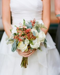This wintry bouquet is made with 'Polo' roses, white ranunculus, brunia, freesia, seeded eucalyptus, and pepperberries