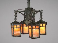Ca. 1906 Arts & Crafts four-light 'Monk' fixture attributed to 'Bradley & Hubbard'.  Predominantly hand made with hammered bronze body and lantern shades.   An unusual design embodied in the original 'Verdigris' finish and fitted with period correct caramel slag glass.  Note that all parts, the chain, canopy and fittings are matching and hand-hammered.
