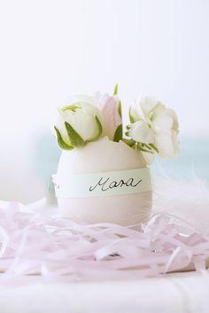 Romantische Oster-Deko: Die Eier beim Backen oder Eier-Auspusten nur an der Spitze aufschlagen und auswaschen, kurzgeschnittene kleine Rosen hineinstellen. Papierstreifen mit den Namen der Gäste beschriften, um die Eier wickeln und mit Draht oder Kleber befestigen. http://www.meine-familie-und-ich.de/ burdafood.net/Gaby Zimmermann