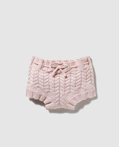 Cubrepañal de tricot en color rosa con detalle de cordón en la cintura para ajustar. Incluye una bolsa en color blanco con detalle de puntilla.