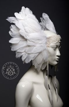 This fierce feather headdress with wing-like structures makes any outfit lift off the ground. It is sturdily build with lots of beautiful white goose feathers, sewn onto a strong base. The headpiece has long feather tassels made of satin ribbon. A bird skull metal pendant decorates the