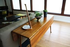 So clever this dining table compress with fold down sides to a sideboard, love a table positioned behind a couch anyway! Yum.