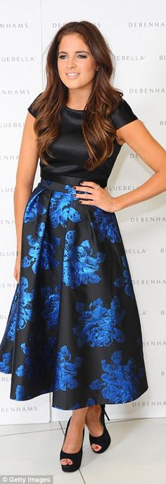 Her look: The Made In Chelsea babe wore in a black satin blouse and a high-waisted skirt, which featured metallic blue floral prints
