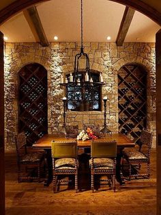 Ornate stone and wood wine cellar with exposed wood beamed ceiling and tasting table for six people.