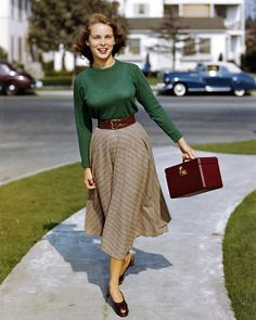 This picture has been attributed to be of Janet Leigh (1927-2004), seen wearing brown flats, a green long sleeve T-shirt, a brown thin waist belt, and a beige and white stripe waist-high knee length circle skirt (ca. 1948).