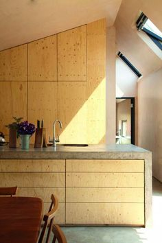 plan de travail en béton ciré, armoires et revêtement mural en bois clair