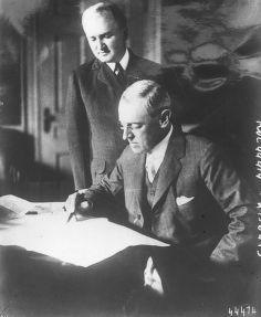 1915 - Le président Wilson écrit la note américaine à la Grande-Bretagne, le secrétaire de Mr Wilson Mr Joseph Tumulty (debout derrière le président assis à son bureau) : photographie de presse / Agence Rol
