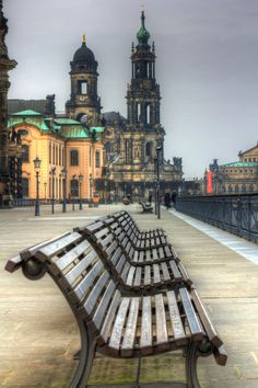 A freezing Saturday morning on the Elbe riverside in Dresden, Germany. The line of empty benches leads the eye to the Holy Trinity Cathedral
