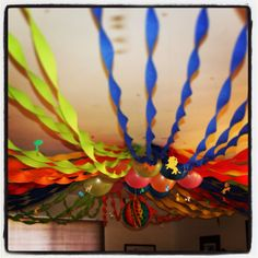 Alternating colors, taped the streamers in the middle of the room and stretched them across the room to create a circus big top look. Balloons in the middle to finish the look.