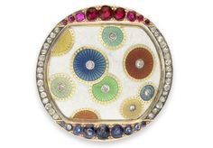 A gem set and enamel brooch by Fabergé's workmaster Henryk Wigström, ca. 1900. Its central white opaque enamel plaque is enriched with vari-coloured overlapping and stand-alone diamond centred enamel discs over a guilloché ground. This is within a diamond, ruby and sapphire-set mount. There was a cigarette case decorated with similar discs in the Forbes Collection.