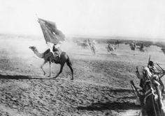 Auda's flag bearer leads the Arab entry into Akaba, Palestine, on July 6, 1917. - in the movie Lawrence of Arabia, Anthony Quinn played Auda.