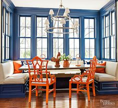 Choose midtone paint colors that provide a punch without overshadowing a space. Glossy delft blue paint makes a good-cheer statement that draws attention to this bay's windows, woodwork, and paneled banquette. The blue hue and complementary orange furnishings combine to create a high-energy design that is both zesty and welcoming./