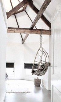 Bijzondere ruimte op zolder met mooie houten balken. De ruimte loopt rond en heeft een glazen puntdak. Een balk is gebruikt om een mooie hangstoel aan te hangen