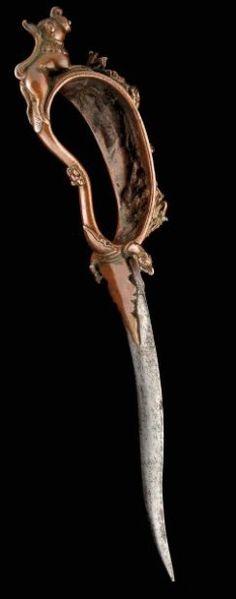 Poignard Magnifique poignard rituel. La lame en fer imbriquée dans un extraordinaire manche en bronze à patine brune profonde, orné de deux petits quillons, terminés par des têtes d'animaux mythologiques. La garde très élaborée comporte trois parties principales. La partie inférieure représente une divinité agenouillée, la partie centrale représente une divinité debout, à tête de cheval portant à chacun de ses 4 bras, un attribut différent, la tête couronnée par 5 cobras.