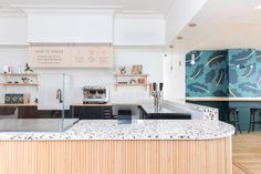 Pastel hues decorate B-Natural Kitchen by Atelier Cho Thompson Black Bar Stools, Natural Kitchen, Pink Cushions, Terrazzo Flooring, Bar Seating, White Tiles, Pink Walls, Patio Chairs, Interior Design