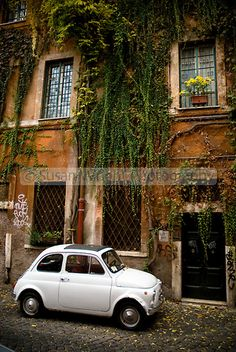 White Fiat Bambino parked in cobble stoned street in Trastevere district of Rome, Italy