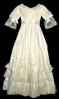 Silk satin wedding dress with cream silk net overlay and wide Brussels lace, fancy embroidery and wide satin ribbon decoration, English, 1833. Worn by Emma Talbot, who was married at Penrice Castle on June 18th, 1833.