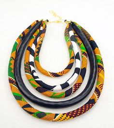 This beautiful orange, green, yellow & black statement necklace is made by hand with Kente Prints, vegan leather and African wax prints.  This