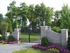 The contrast of the gray stone fence and black iron gate gives an elegant look with a strong feel.