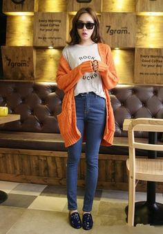 Cute street style outfit with the graphic white tee, the blue skinny jeans, and the oversized orange cardigan.