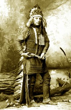 Oglala Sioux Chief Red Shirt poses for a full-length studio portrait while touring with Buffalo Bill's Wild West Show. Photograph taken between 1885 and 1900.