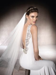 MARA is a unique wedding dress with spectacular gemstone embroidery on the back and shoulders. A crepe design with a bateau neckline