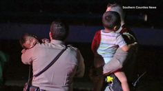 CHP officers hold two children who were injured in a crash in Santa Ana on Monday, April 13, 2015.