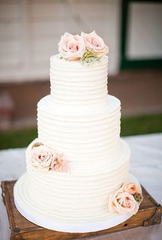 A three-tiered white wedding cake decorated with pale pink roses, created by Beverly's Best Bakery.
