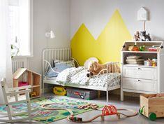 Chambre d'enfant avec lit extensible MINNEN adossé à un mur, à côté de la table à langer SUNDVIK. Un circuit de petit train est installé par terre.
