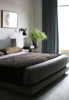A Modern Tribeca Home That Mixes Comfort and Style: In the master bedroom, natural surfaces and light balance the bedroom's modern features. A unique, stone gray bark paper covers the walls in a subtle pattern. The oak floor is accented with an alpaca and cashmere slate blue rug, and natural light from the floor-to-ceiling windows offsets the gray tones throughout the room. #NYCapartment #Manhattanapartment