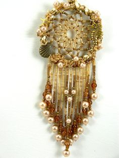 Beach themed Tan and cream hand beaded dream catcher. A very unique gift for yourself or that special person in your life! 6 1/2 inches in length from top of hoop to bottom of fringe. Created on a 2 1/2 inch brass hoop Made up of glass pearls, seed beads, satin cord, and metal components . center is made up of glass seed beads BDC#5 The legend of the dream catcher varies from tribe to tribe, but the basic intention is to allow good dreams to slip through the center hole and into ...